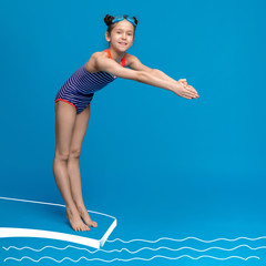 Cute girl about to dive off diving board into swimming pool