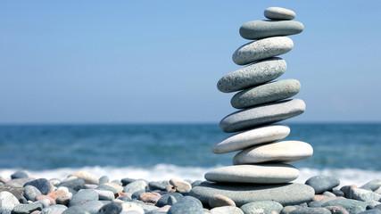 folded pyramid of smooth stones on the seashore.