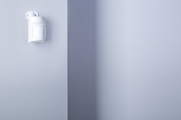 Motion sensor for security system mounted on wall.