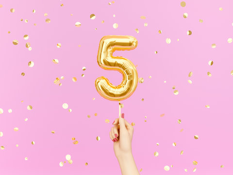 Five year birthday. Female hand holding Number 5 foil balloon.  Five-year anniversary background. 3d rendering