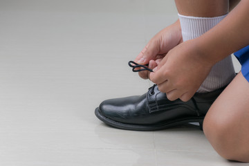Asian boy wearing his school uniform ready to go back to school and tying his shoe. Back to school concept with copy space for text.