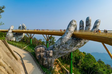 Poster de jardin Ponts The Golden Bridge. The two giant colossal hands emerging from the mountains holding up the golden bridge at the height of 1,414 m from the sea level in Ba Na Hills. Vietnam.
