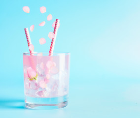 Summer beverage with rose petals and flowers. Refreshment drinks. Iced lemonade or cocktail on blue background