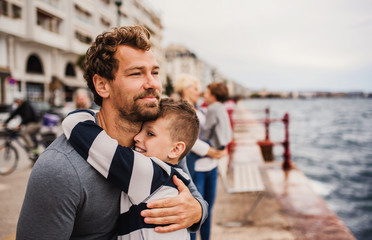 Father with small son standing outdoors in town by the sea, hugging. Wall mural