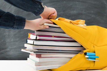 Information overload. Closeup of kid hands packing books into backpack. Chalkboard background.
