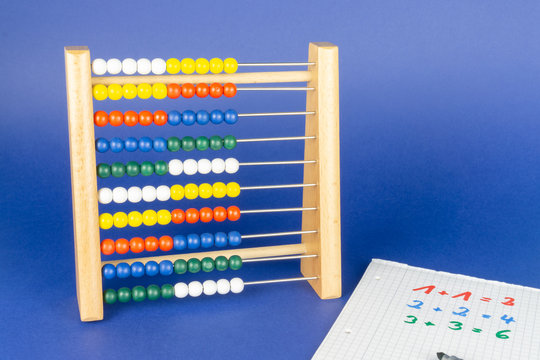 A slide rule with colorful balls and a calculating block, blue background and copy space