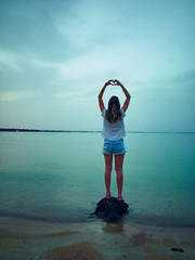 Woman making heart - shape with hands on a ocean / sea shore.