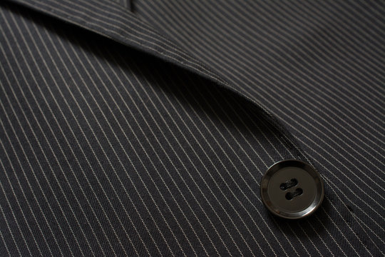Detail of closeup of suit button on pin stripped cloth. Tailoring background