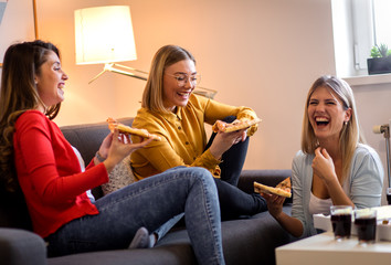 Three female friends chatting and enjoying eating pizza at home.