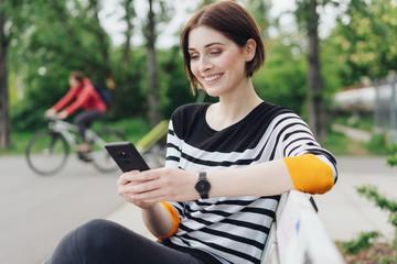lächelnde frau sitzt im Park und schaut auf ihr Mobiltelefon