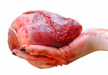 A hand is holding a real human heart with blood on a white background. The heart is stitched with thread