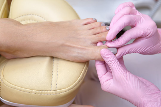 Closeup of pedicure master rubs oil into the cuticle on the nails of the client. Therapist doing massage of fingers