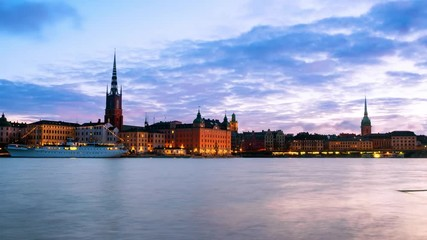 Wall Mural - Stockholm, Sweden. Time-lapse of Gamla Stan in Stockholm, Sweden with landmarks like Riddarholm Church during the sunrise. View of old buildings and cloudy sky in morning