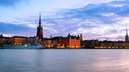 Wall Mural - Stockholm, Sweden. Time-lapse of Gamla Stan in Stockholm, Sweden with landmarks like Riddarholm Church during the sunrise. View of old buildings and cloudy sky in morning, zoom in