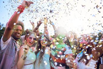 Friends celebrating holi festival under shower of confetti