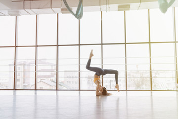 Foto op Aluminium Luchthaven young attractive girl doing fitness exercises with yoga on the floor against the background of panoramic windows
