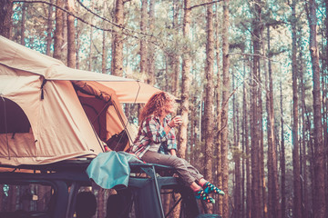 Happy free alternatie vacation traveler people - cute blonde sit down on the roof of the car with tent drinking coffee and enjoying the beauty of the forest around - wanderlust lifestyle girl