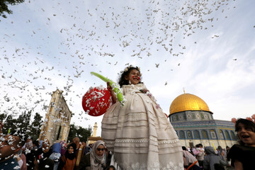 Foam is sprayed as a girl smiles during celebrations after Palestinians performed Eid al-Fitr prayers which marks the end of the holy fasting month of Ramadan, in Jerusalem's Old City