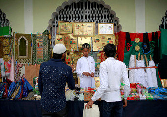 A boy sells religious goods to the customers at a mosque before the Eid al-Fitr prayers to mark the end of the holy fasting month of Ramadan, in Kathmandu