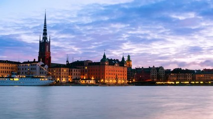 Fototapete - Stockholm, Sweden. Time-lapse of Gamla Stan in Stockholm, Sweden with landmarks like Riddarholm Church during the sunrise. View of old buildings and cloudy sky in morning, panning video