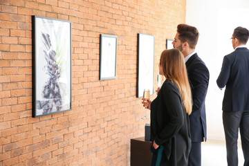Couple at exhibition in modern art gallery