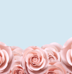 .pink roses at the bottom on a blue background. Place for inscription.
