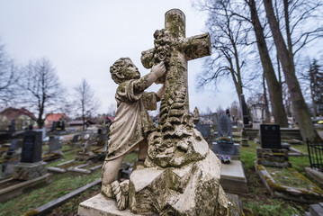 Grave on the cemetery in front of Virgin Mary old wooden church in Broumov town in Czech Republic