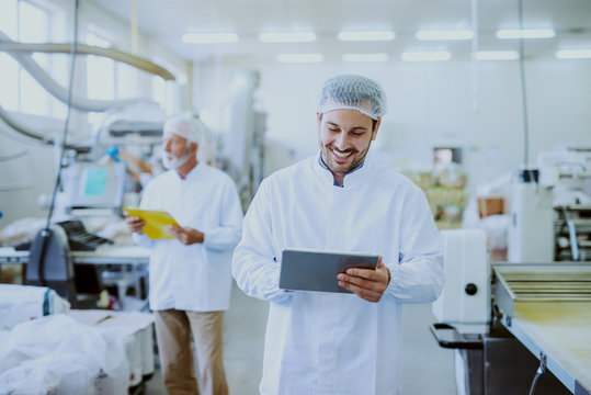 Young Caucasian smiling supervisor in sterile white uniform using tablet while standing in food plant. In background older one worker controlling machine.