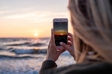 A young girl photographs the sunrise near the sea on a smartphone. A woman is holding a mobile phone. Good morning on the beach. Beautiful sky with sun and sea waves. Travel concept