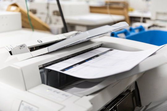 Printshop printer printing out A4 sheets for customer.