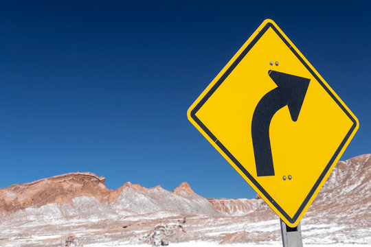 Road turn with yellow road sign in the Atacama desert, Chile
