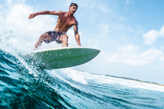 Young surfer with lean muscular body rides the tropical wave