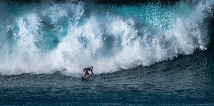 Surfer rides huge wave at the famous Banzai Pipeline surf spot located on the North Shore of Oahu in Hawaii