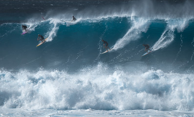 Wall Mural - Four surfers share the giant wave at the famous Waimea Bay surf spot located on the North Shore of Oahu in Hawaii