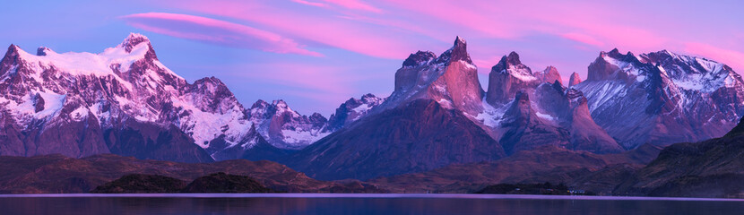Torres del Paine National Park with snow capped mountains (Cordillera Paine) and calm lake of Pehoe at the sunrise Chile