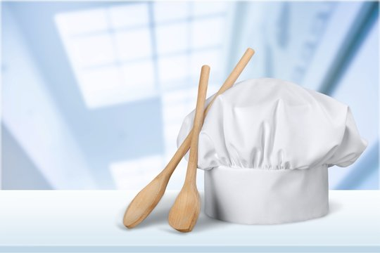 White cooks cap and wooden spoons on wooden table