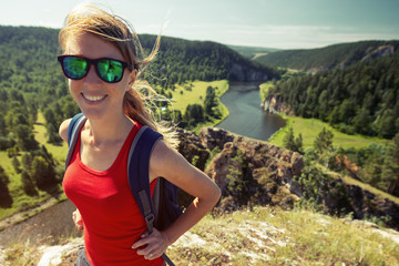 Happy woman with backpack stands on the hill with valley on the background