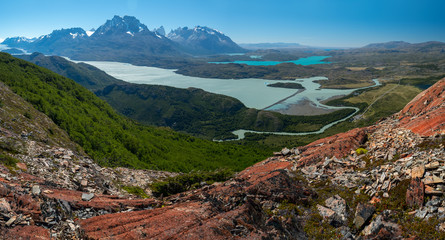 Panorama of the Torres del Paine National Park with rivers, blue lakes, coniferous green forests and snow capped mountains of Cordillera Paine. Chilean Patagonia