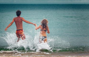Happy couple runs into the sea with splashes