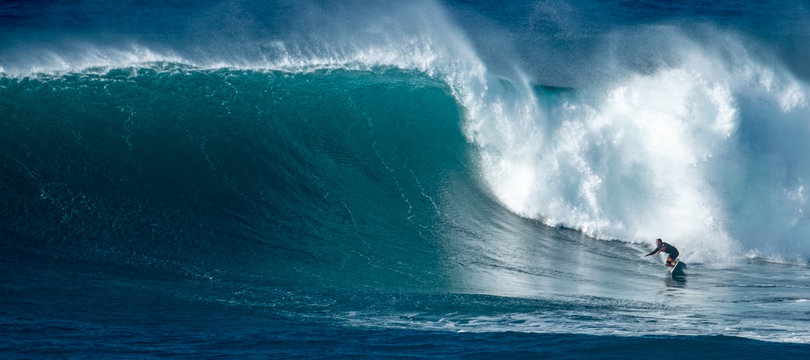 Surfer rides giant wave at the famous Waimea Bay surf spot located on the North Shore of Oahu in Hawaii