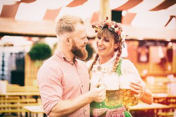 Fototapete - Junges Paar Mann und Frau mit Dirndl und Lederhosen in Festezelt und Maß Bier