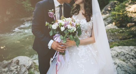 Wedding couple is hugging near the mountain river. Groom and bride with a bouquet in hands. Beautiful flowers. Nature waterfall.