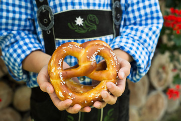 Close up of pretzel in the boy hands wearing a traditional bavarian clothes during Oktoberfest in Germany .