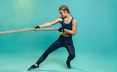 Tough sports woman exercising with battling rope