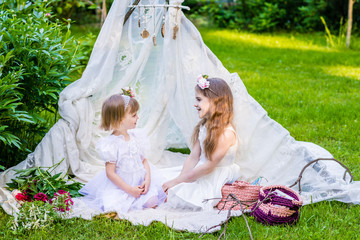 Two sisters in white dresses sit in white boho tent outdoor and look to ech other.