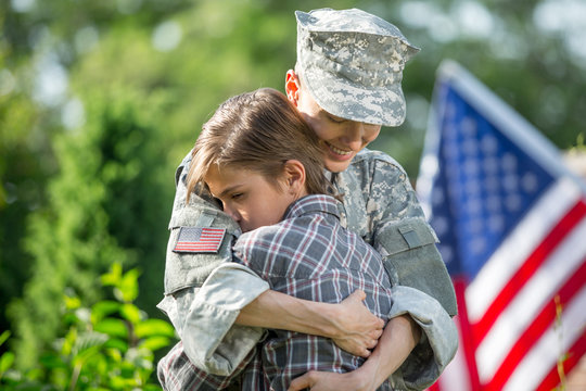 Happy reunion of female mother soldier with family son outdoors