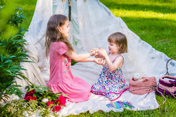Two sisters in multi-colored dresses sit in white boho tent outdoor and play in finger game.