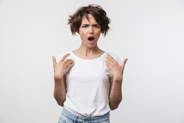 Wall Mural - Shocked woman posing isolated over white wall background pointing to herself.