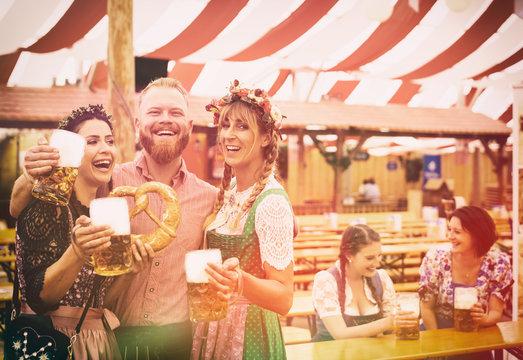 Freunde auf dem Oktoberfest im Bierzelt mit Maß Bier