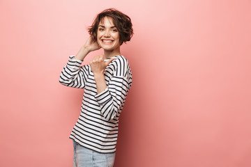 Wall Mural - Happy beautiful woman posing isolated over pink wall background pointing.